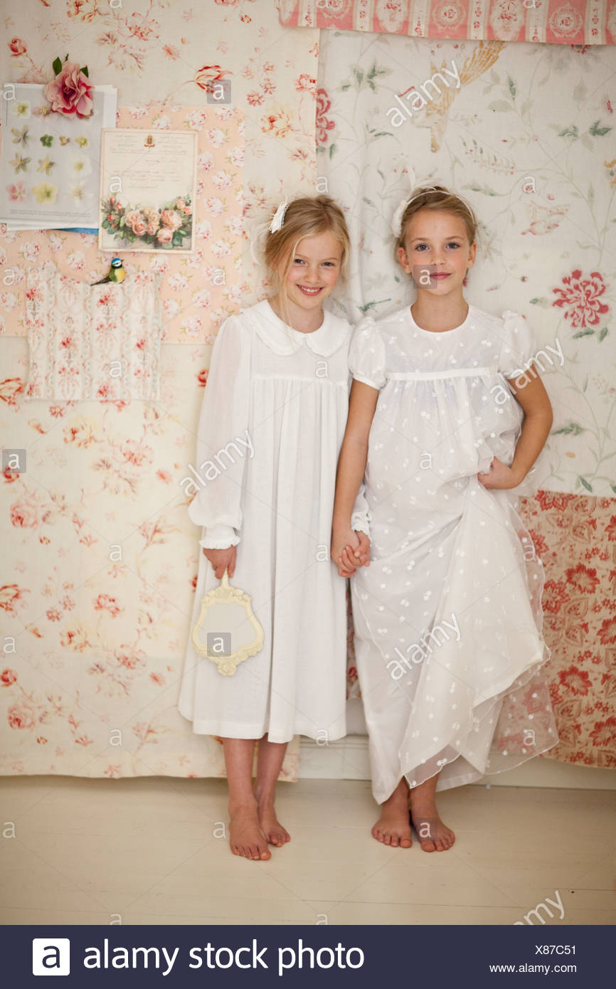 Girls holding hands in bedroom - Stock Image