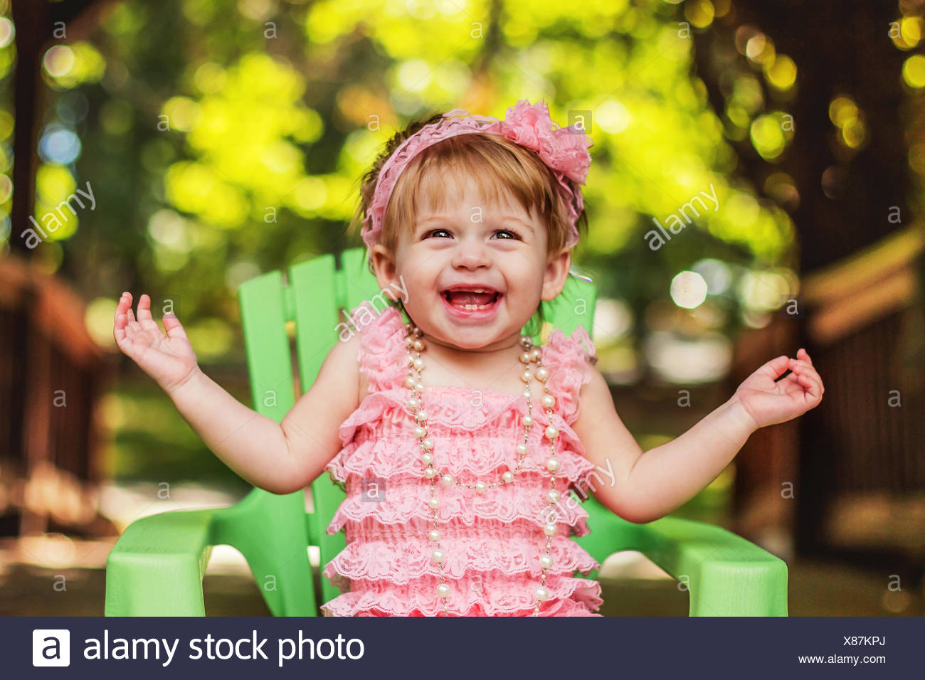 Happy girl in a party dress sitting in garden chair laughing - Stock Image