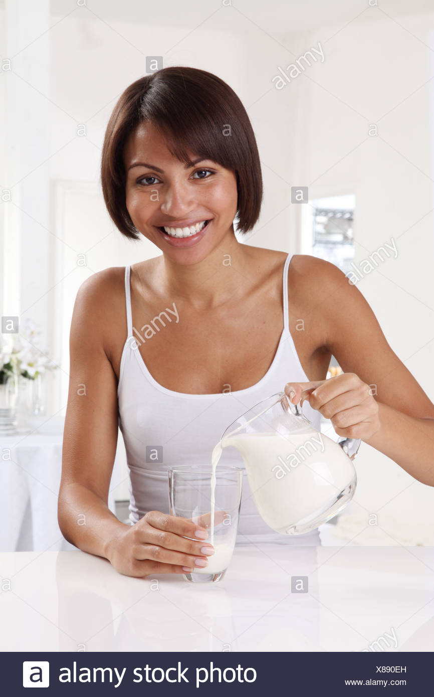 WOMAN POURING MILK INTO GLASS - Stock Image