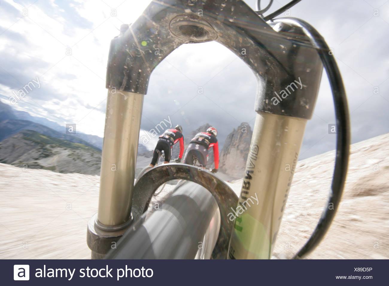 Persons mountain biking near Tre Cime di Lavaredo, Veneto, Italy - Stock Image