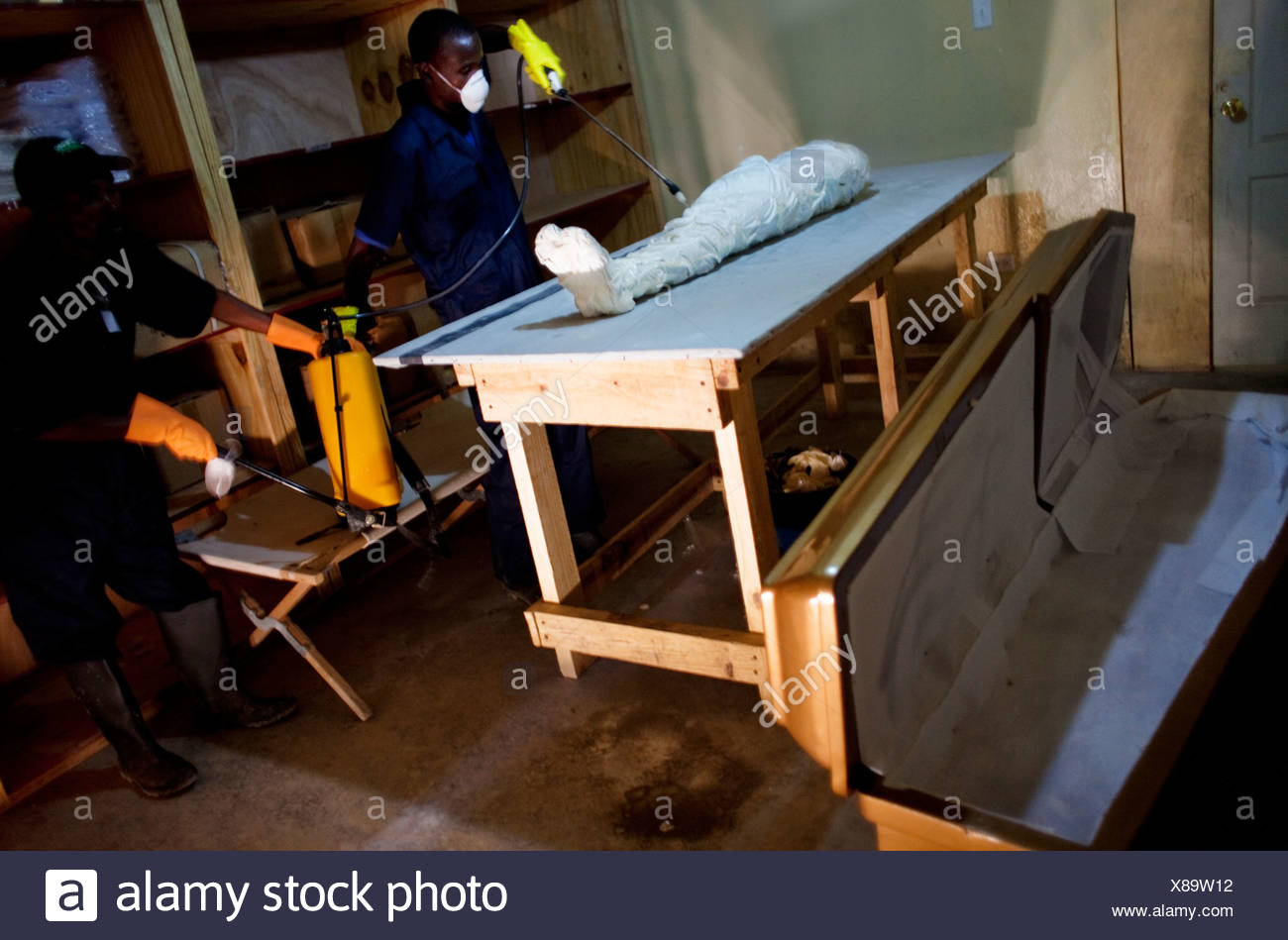 Hospital workers disinfect a cholera corpse. - Stock Image