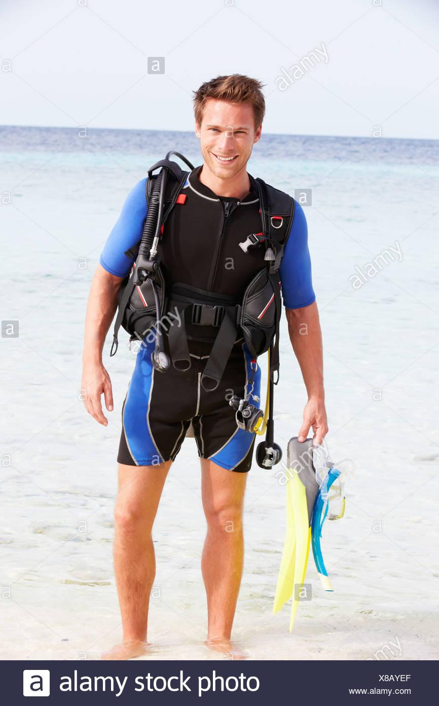 Man With Scuba Diving Equipment Enjoying Beach Holiday - Stock Image