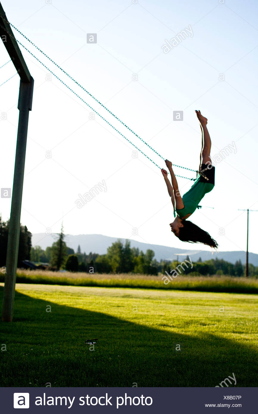 A young women swinging smiles while looking back on a summer evening in Idaho. - Stock Image