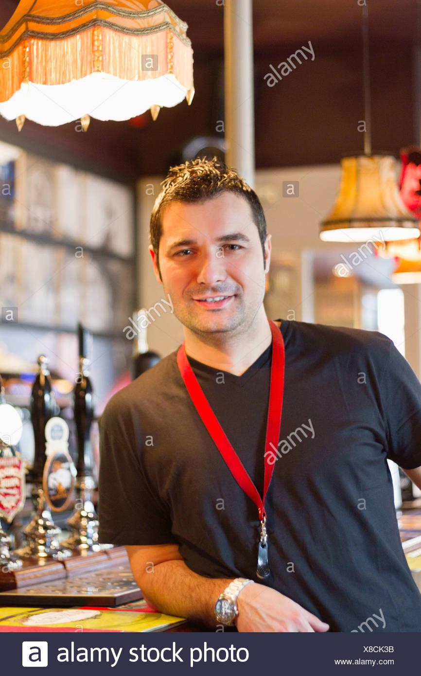 Portrait of smiling pub manager - Stock Image