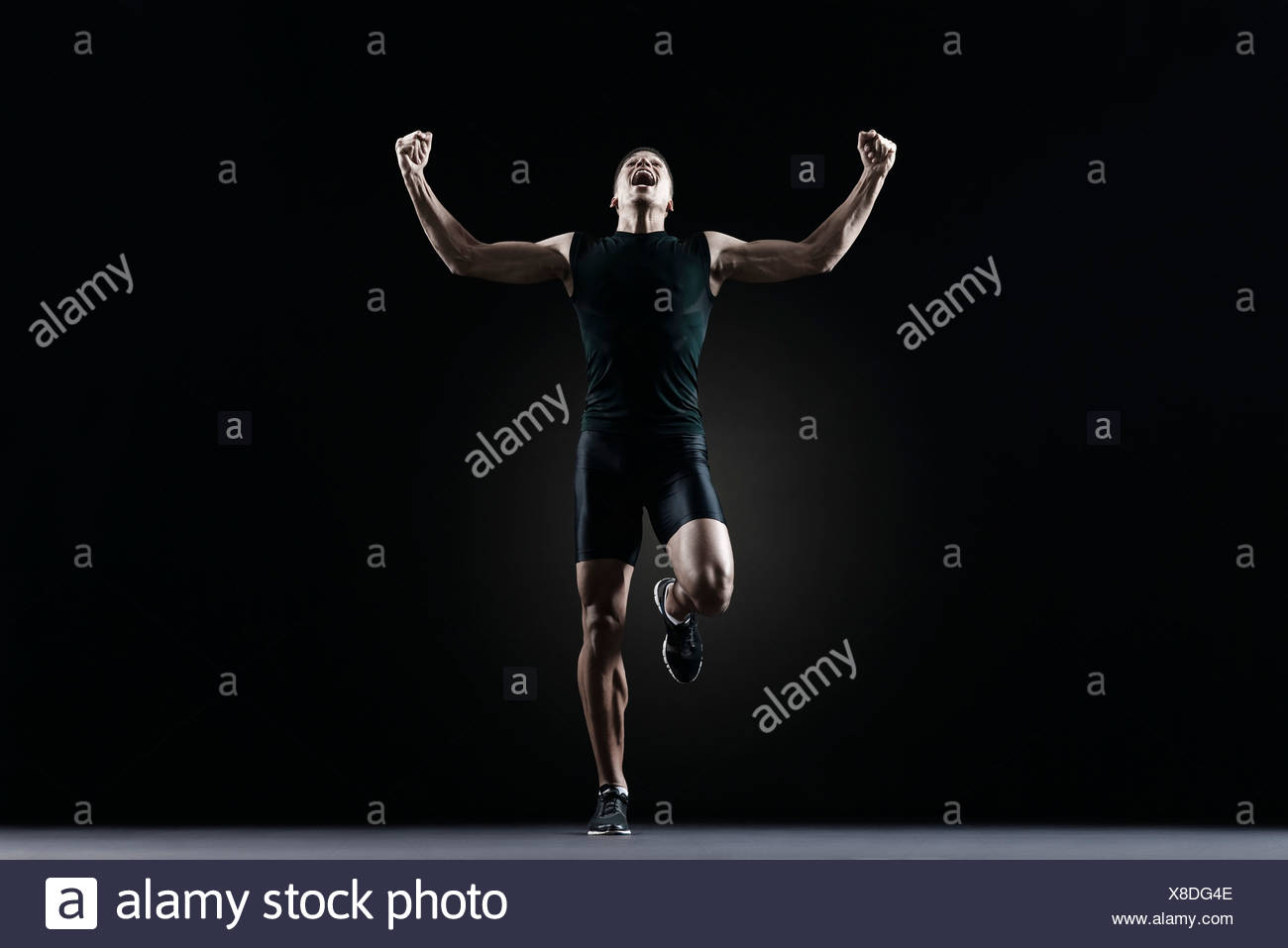 Male athlete flexing arms and shouting - Stock Image