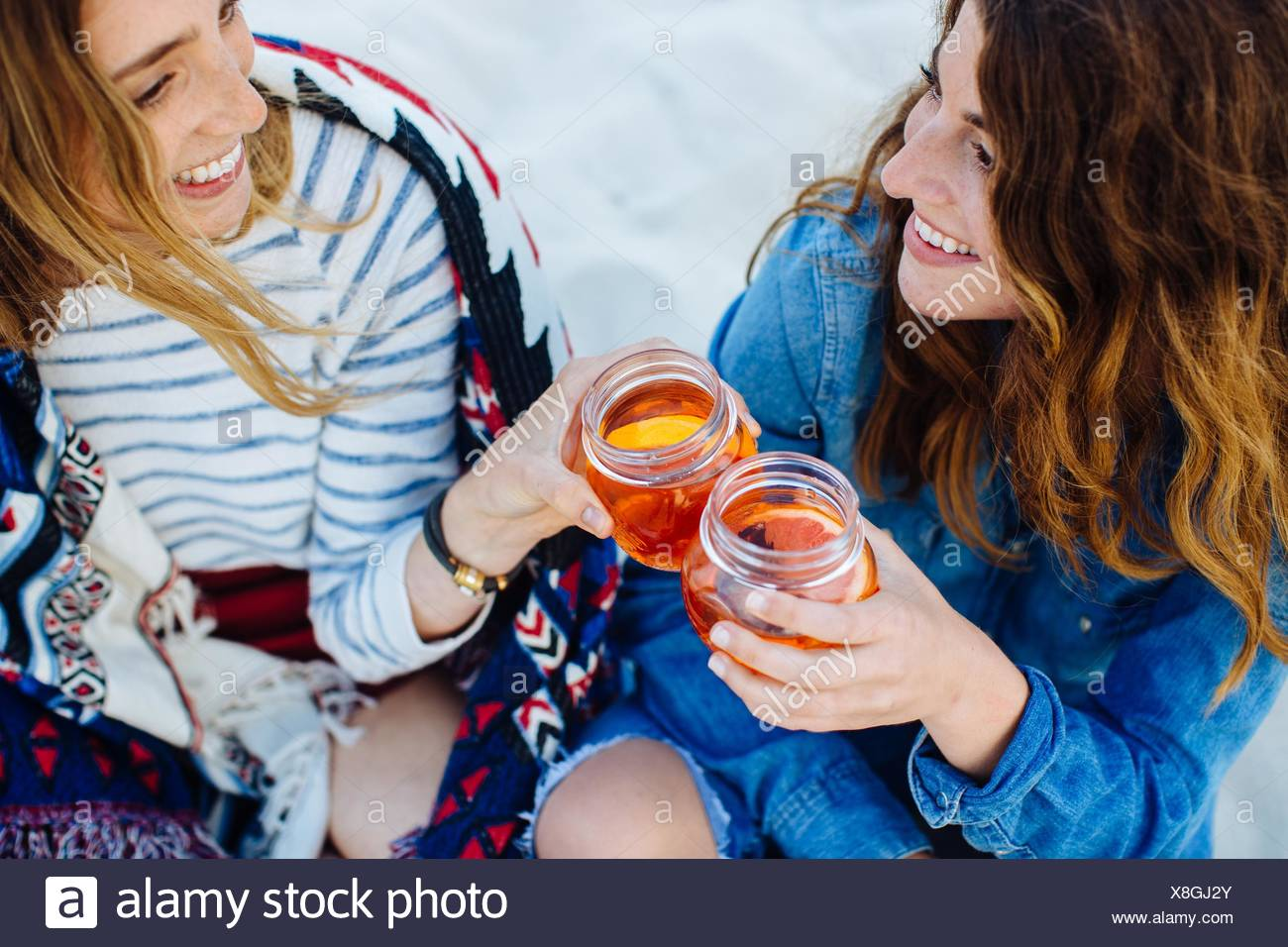 Two young female friends toasting with jar drink on beach - Stock Image