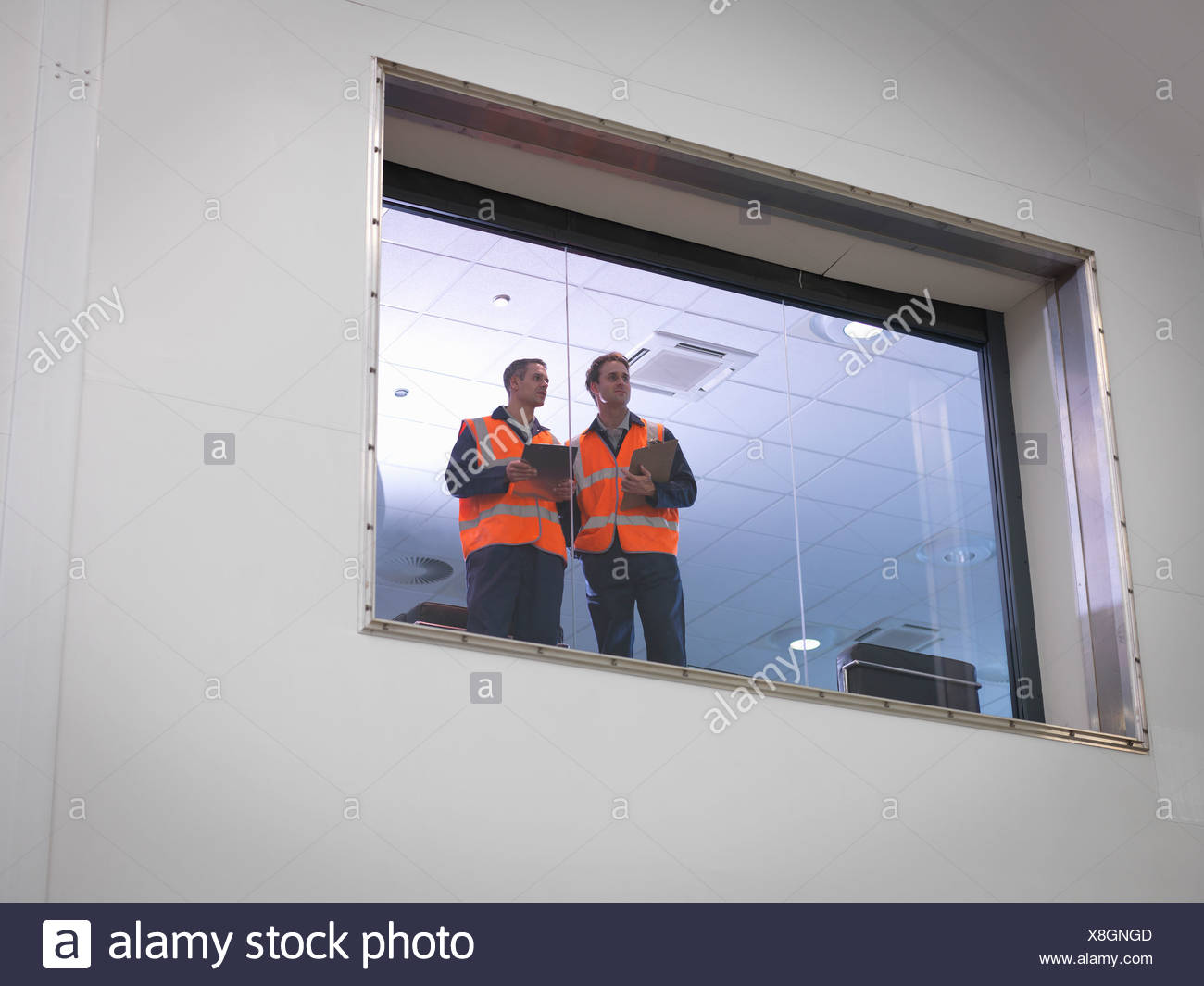 Engineers look out of window into hangar - Stock Image