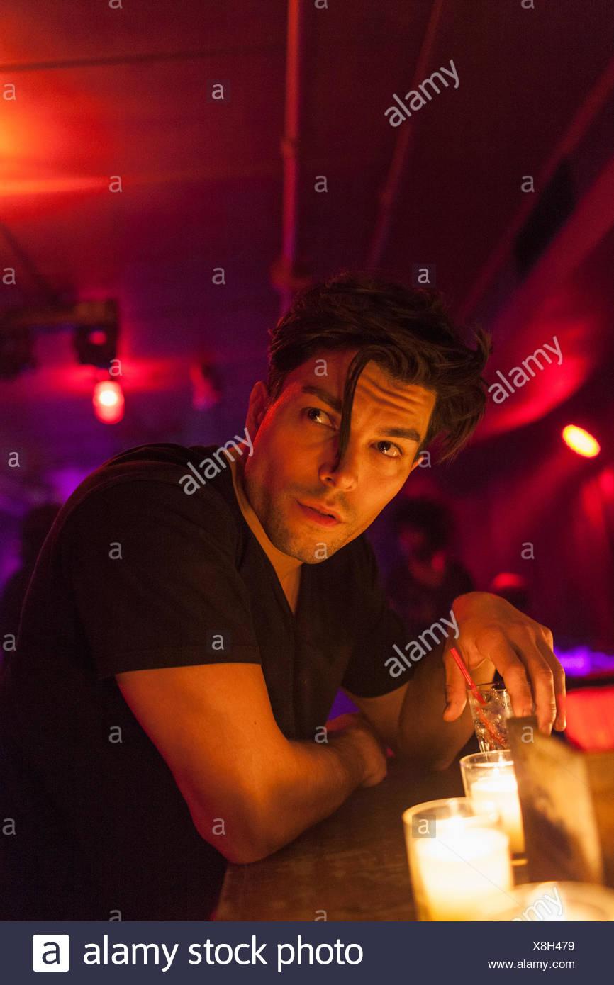 Young man enjoying a drink at a bar - Stock Image