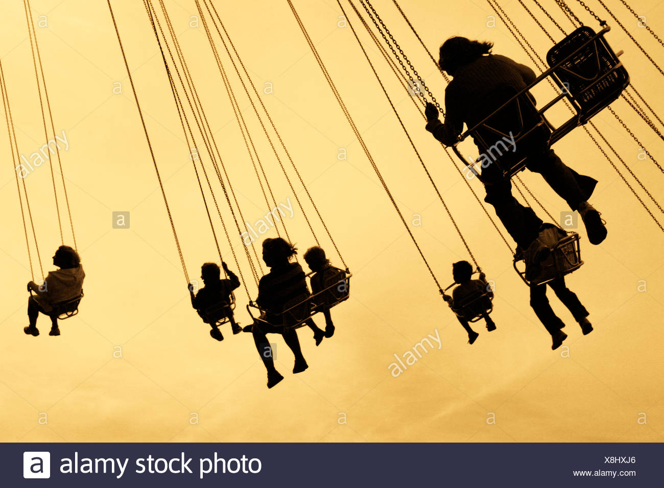 Sweden, Vastra Gotaland, Gothenburg, Silhouettes of people on carousel in Liseberg amusement park - Stock Image