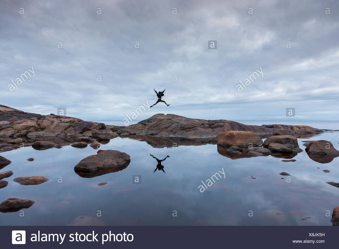 Woman jumping on rock by a lake in Vasterbotten, Sweden - Stock Image