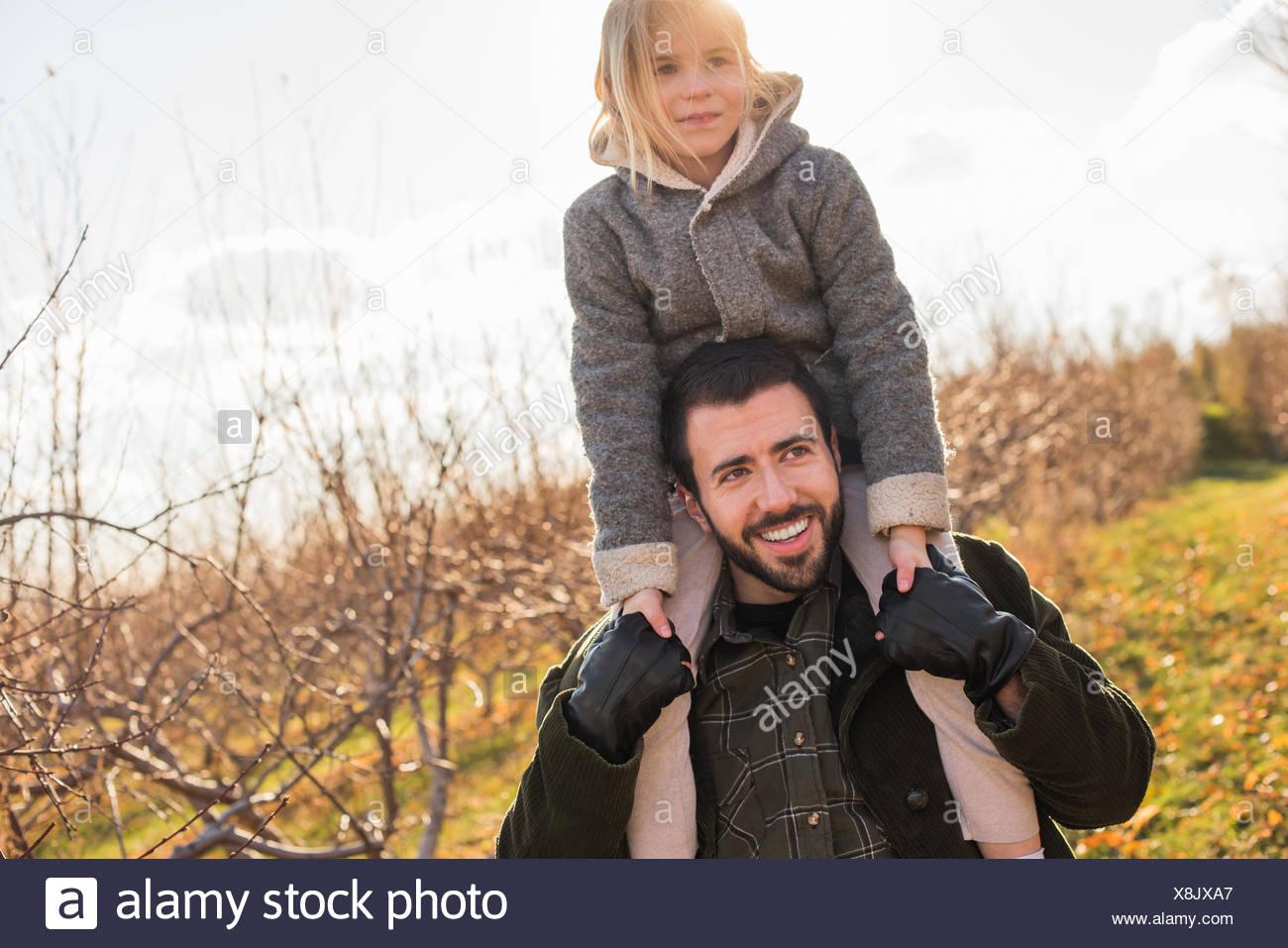 A man giving a child a ride on his shoulders. - Stock Image