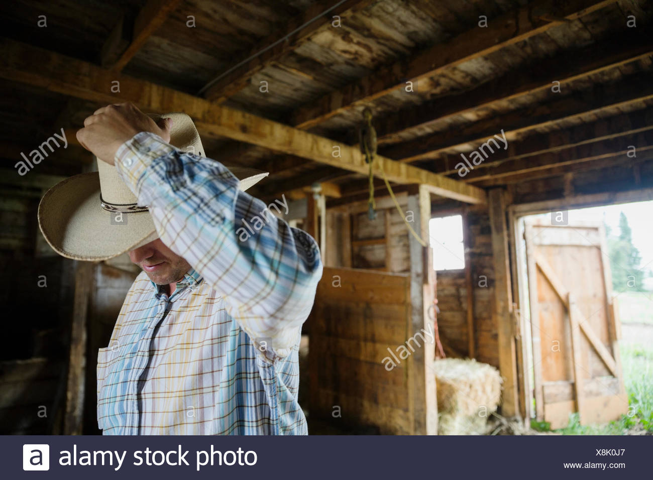 Rancher with cowboy hat in barn - Stock Image