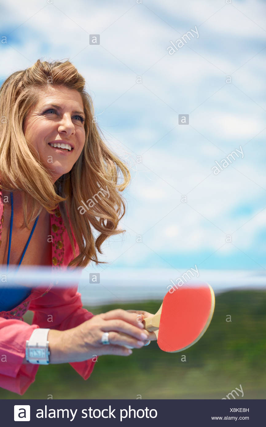 Smiling older woman playing table tennis - Stock Image