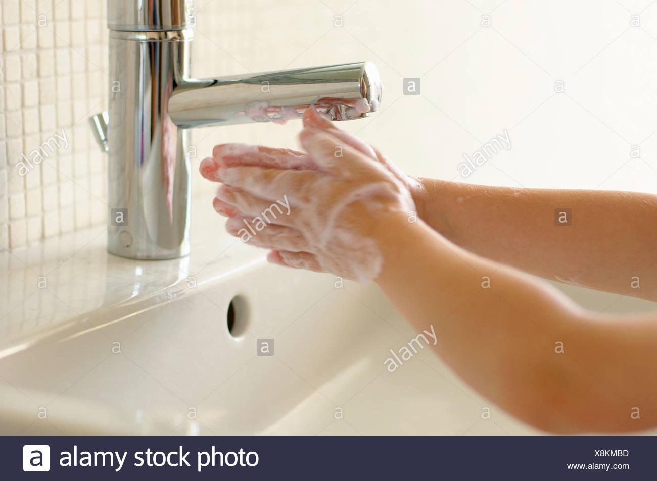 Boy washing hands at sink, Den Haag, Netherlands - Stock Image