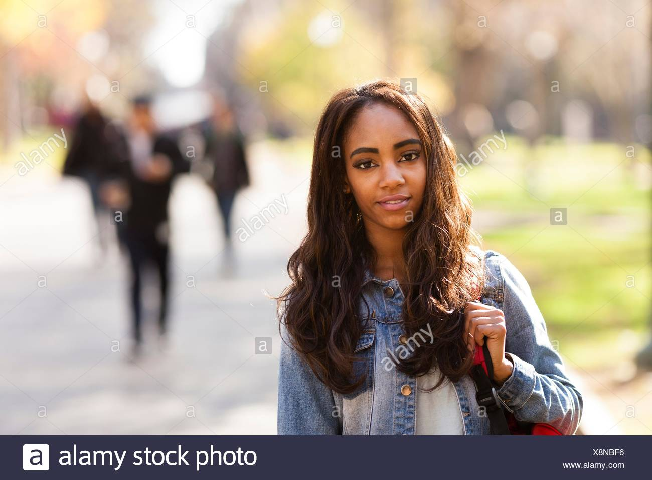 Portrait of young woman with long brown hair wearing denim jacket looking at camera smiling - Stock Image