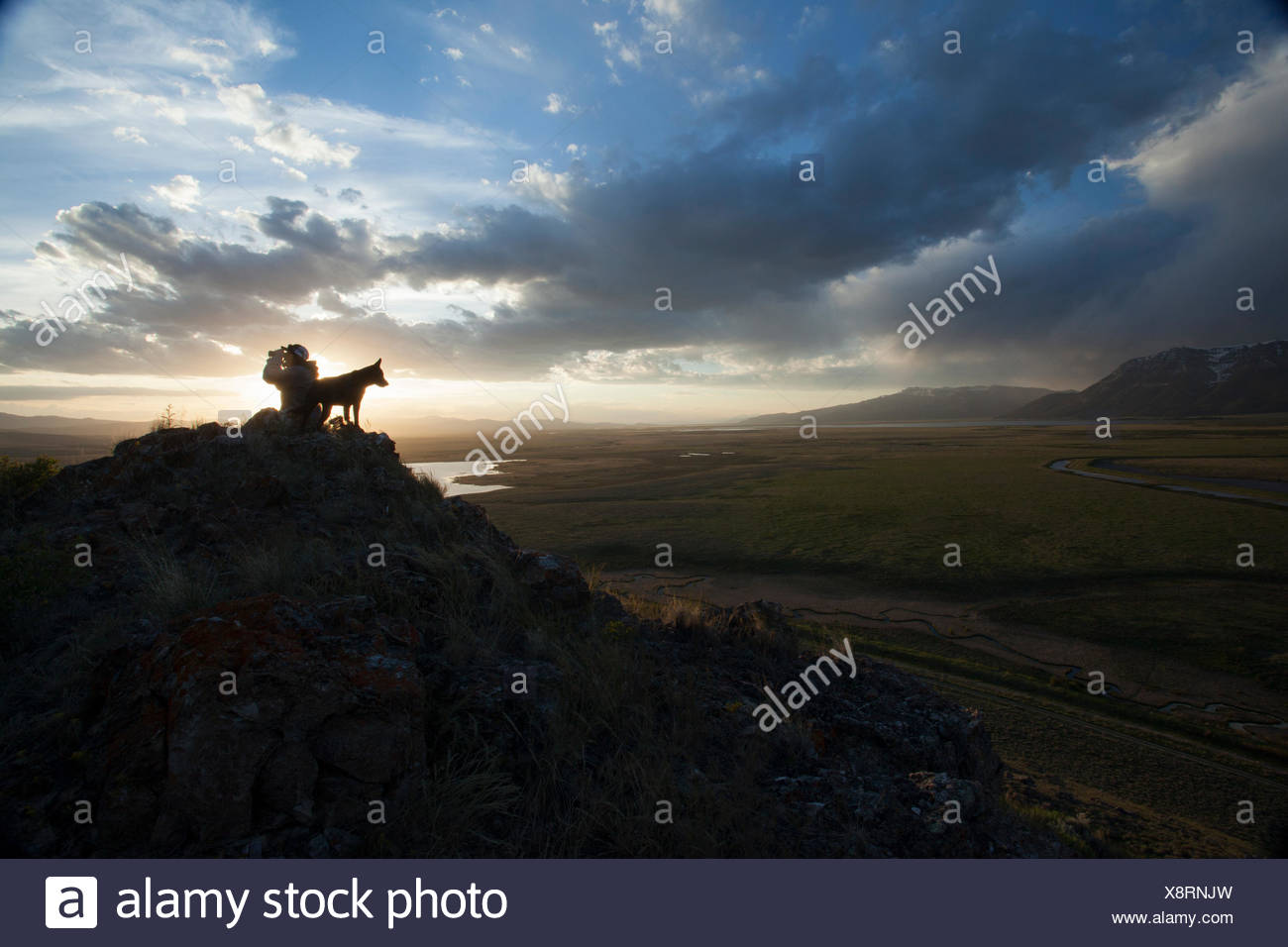 A wildlife tour guide in the Greater Yellowstone Ecosystem takes in the sunset with his dog. - Stock Image