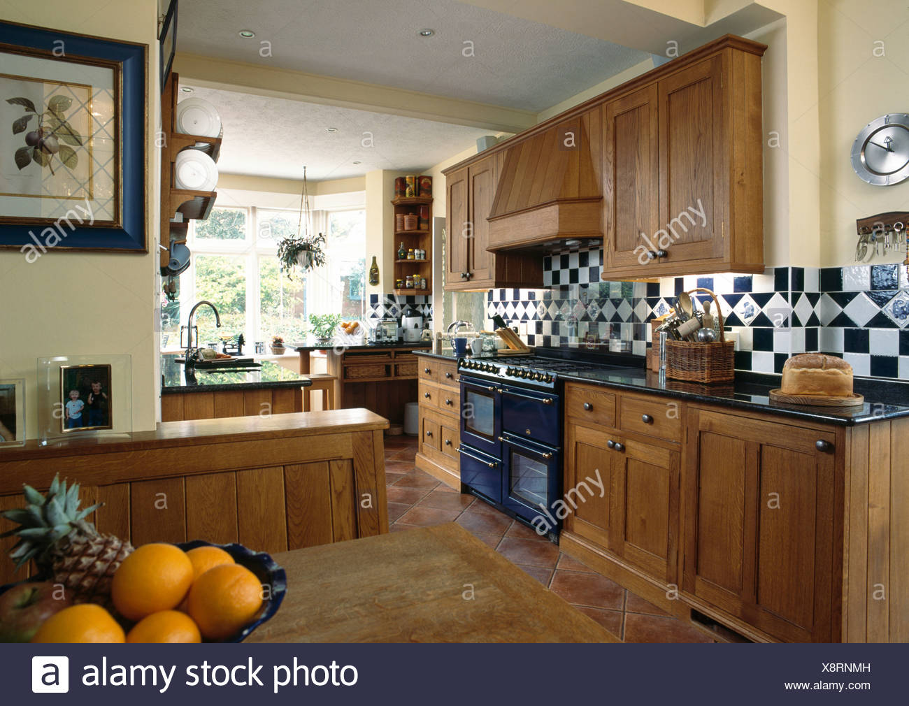 Fitted Oak Cupboards In Large Traditional Country Kitchen With Black