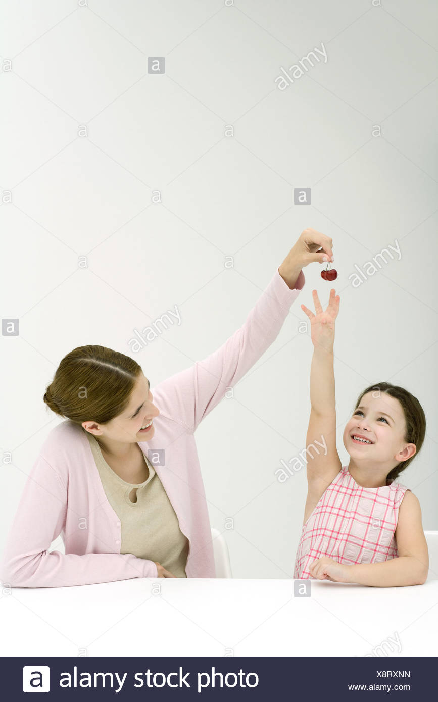 Mother holding up cherries, daughter reaching, both smiling - Stock Image