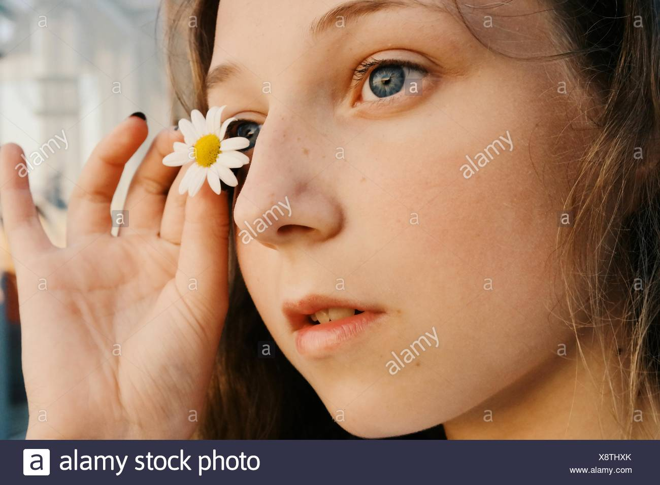 Close-Up Of A Girl Holding A Daisy Flower Near Her Eye - Stock Image