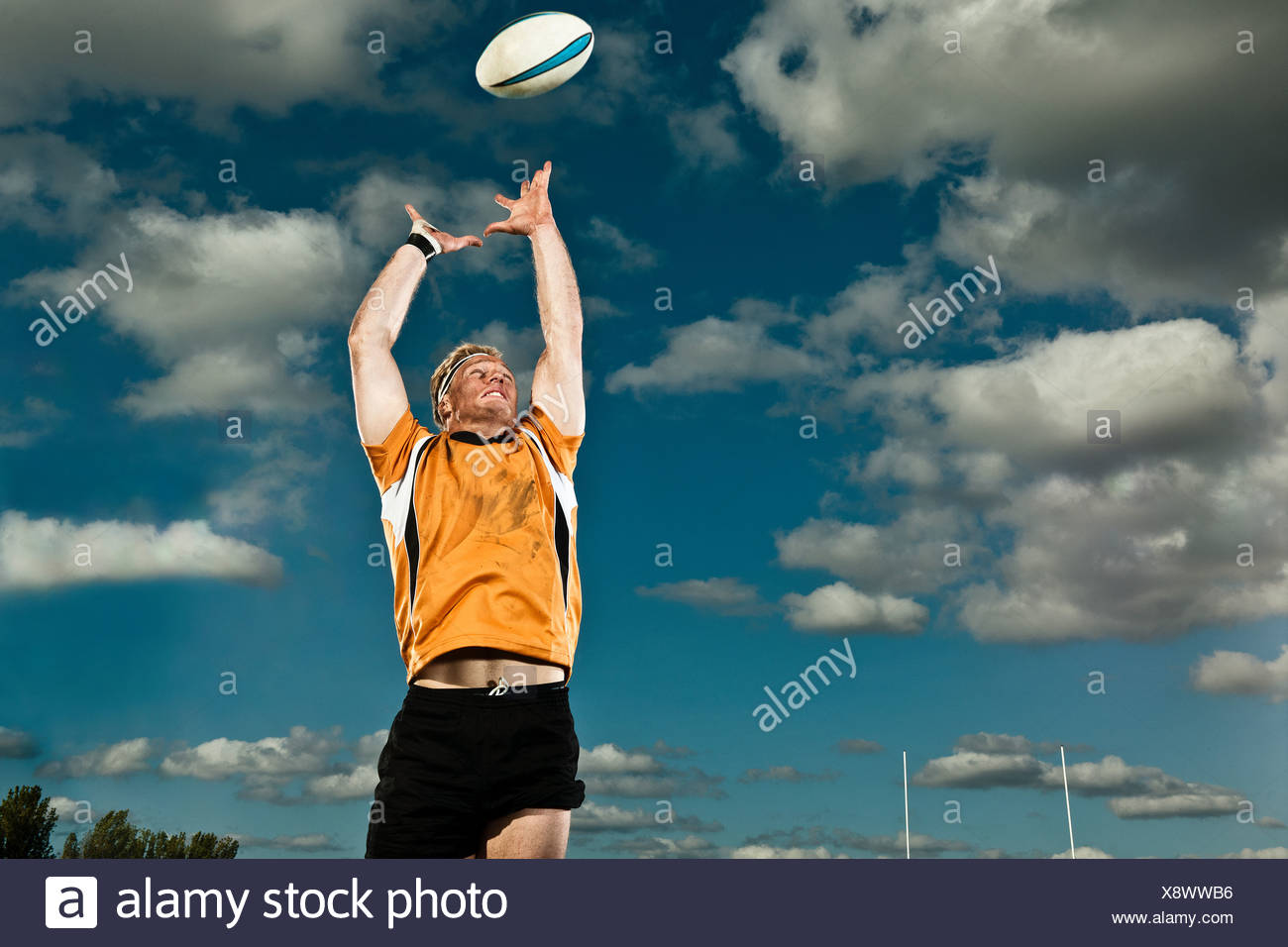 Rugby player leaping up to catch ball - Stock Image