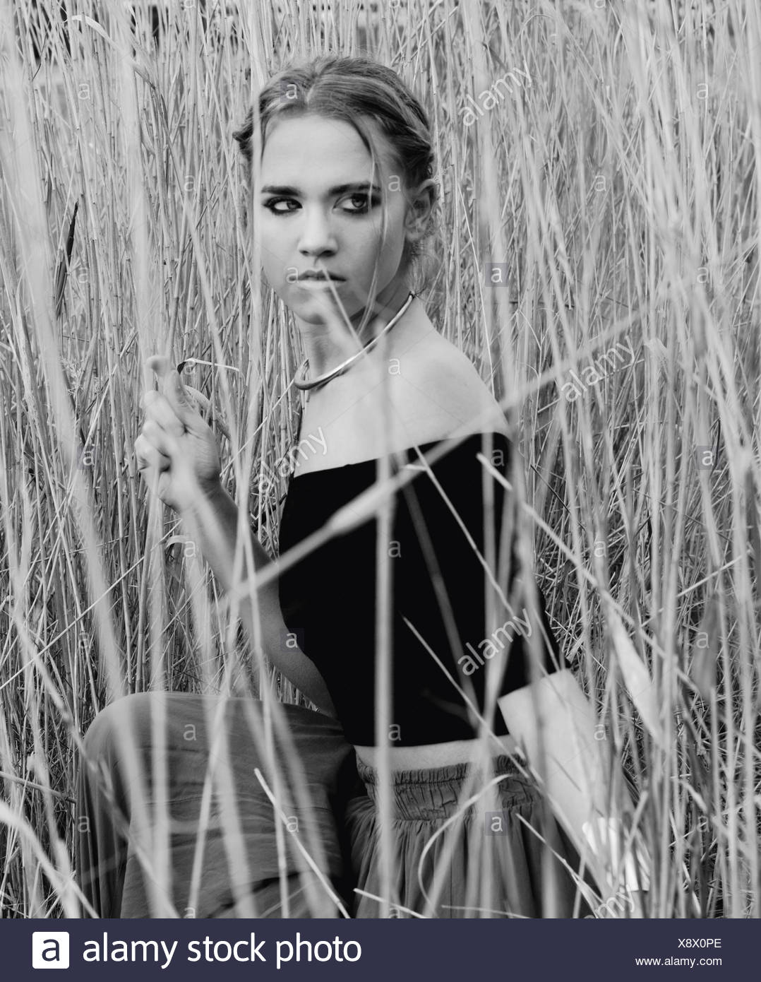 Woman hiding in tall grass - Stock Image