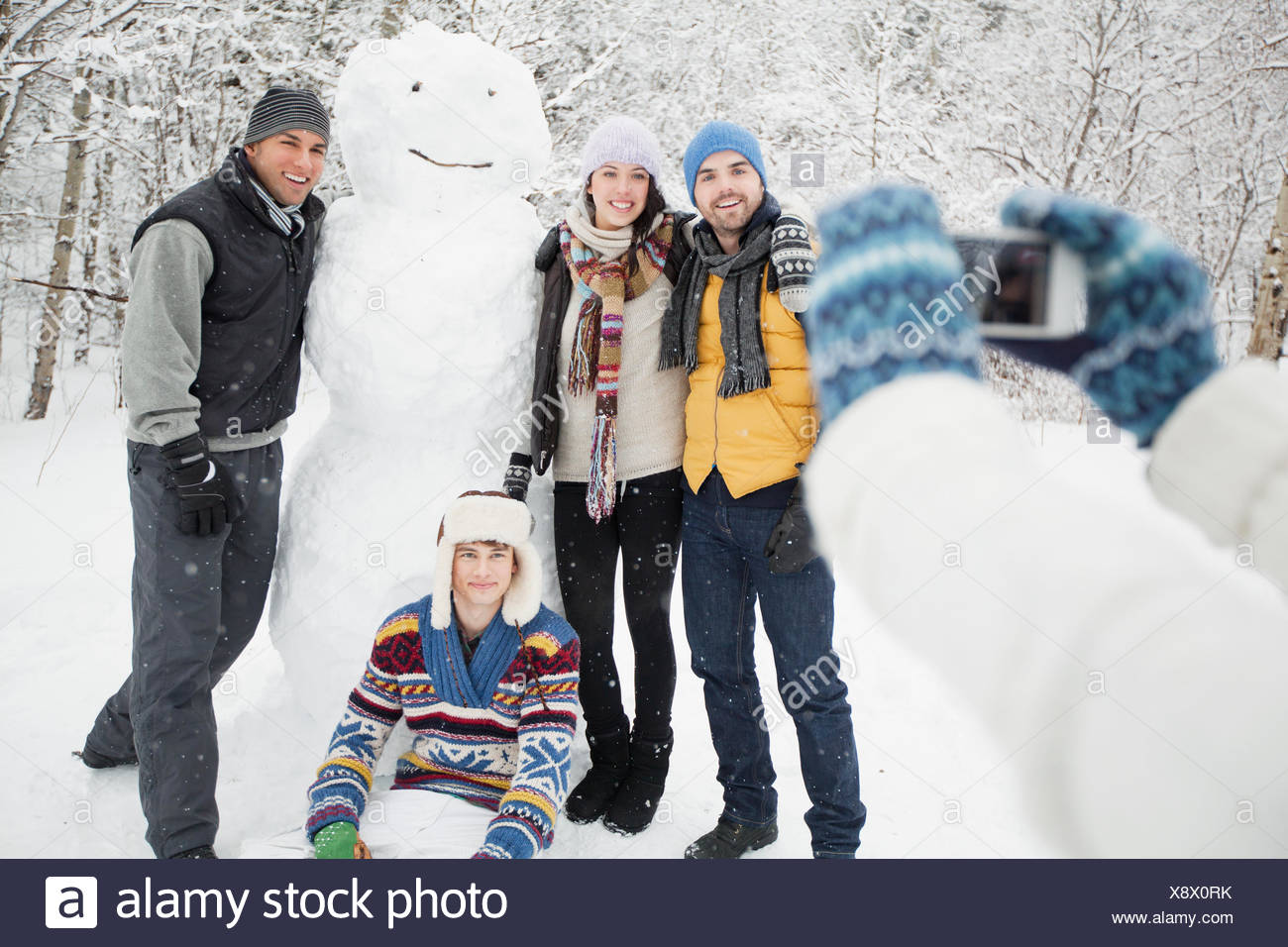 picture taking with snowman - Stock Image