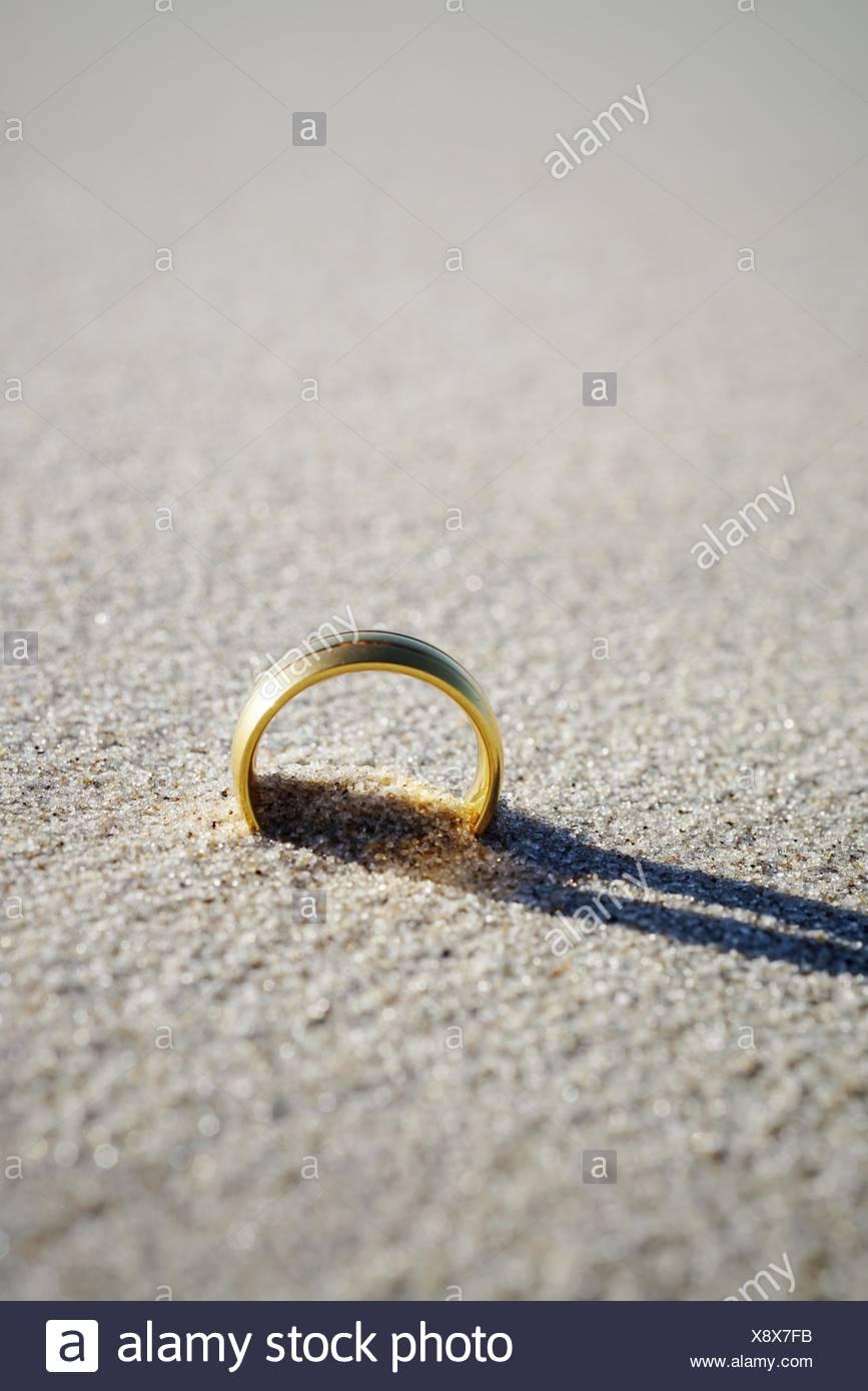 Close-Up Of Wedding Ring On Beach - Stock Image