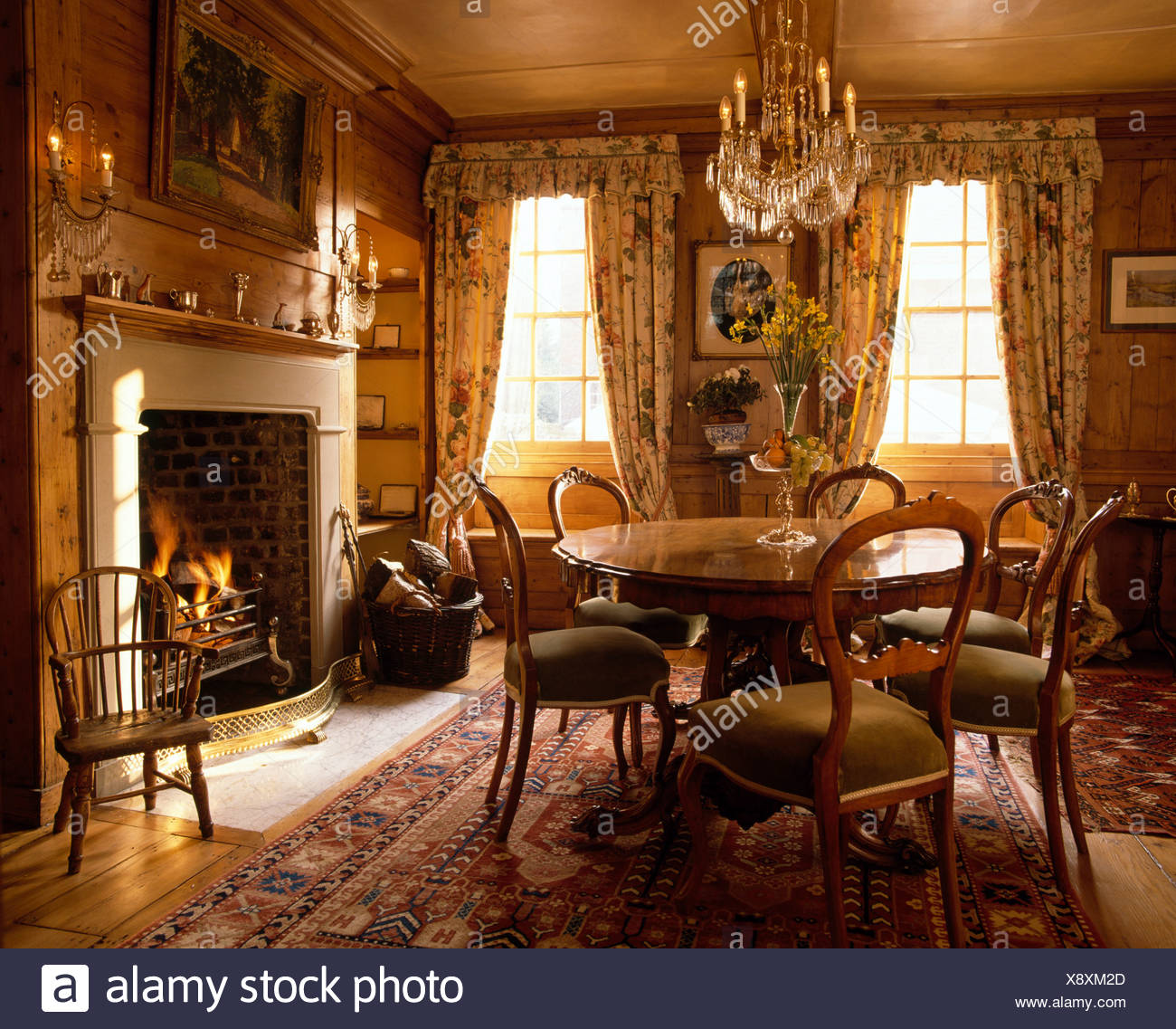 Circular Antique Table With Upholstered Chairs In Diningroom With Fireplace  And Rugs On Polished Floorboards