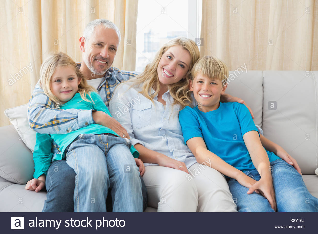 Happy family smiling at camera - Stock Image