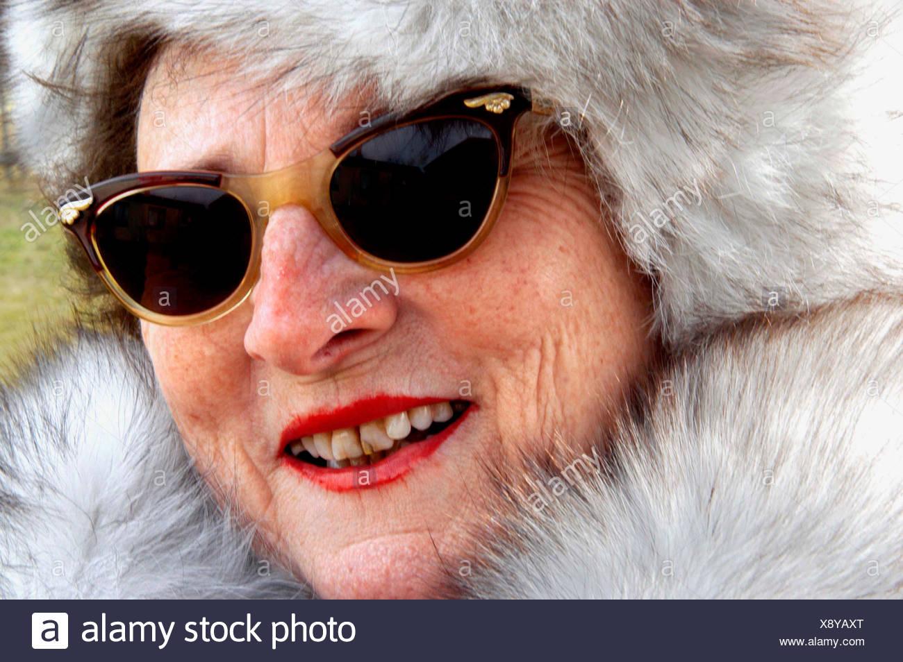 e037dfd60f Old woman in a fur coat with a fur hat and sunglasses Stock Photo ...