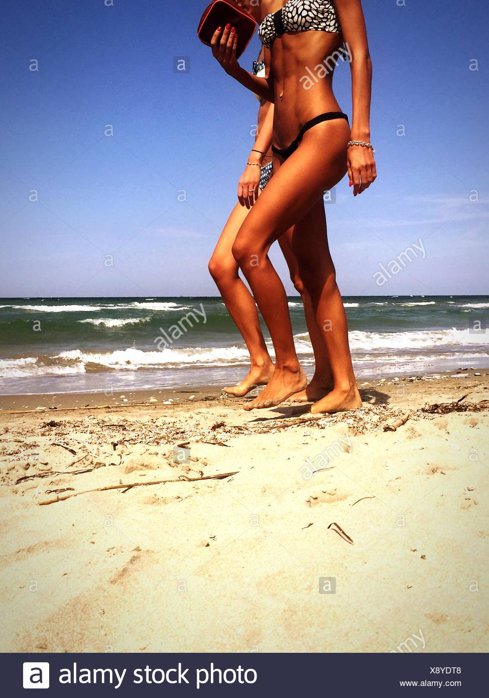 Two Women Walking On Beach - Stock Image