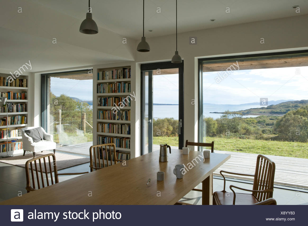 Beau Pale Wood Table And Chairs In Centre Of Modern Open Plan Dining Room With  View Of The Landscape Through Glass Walls