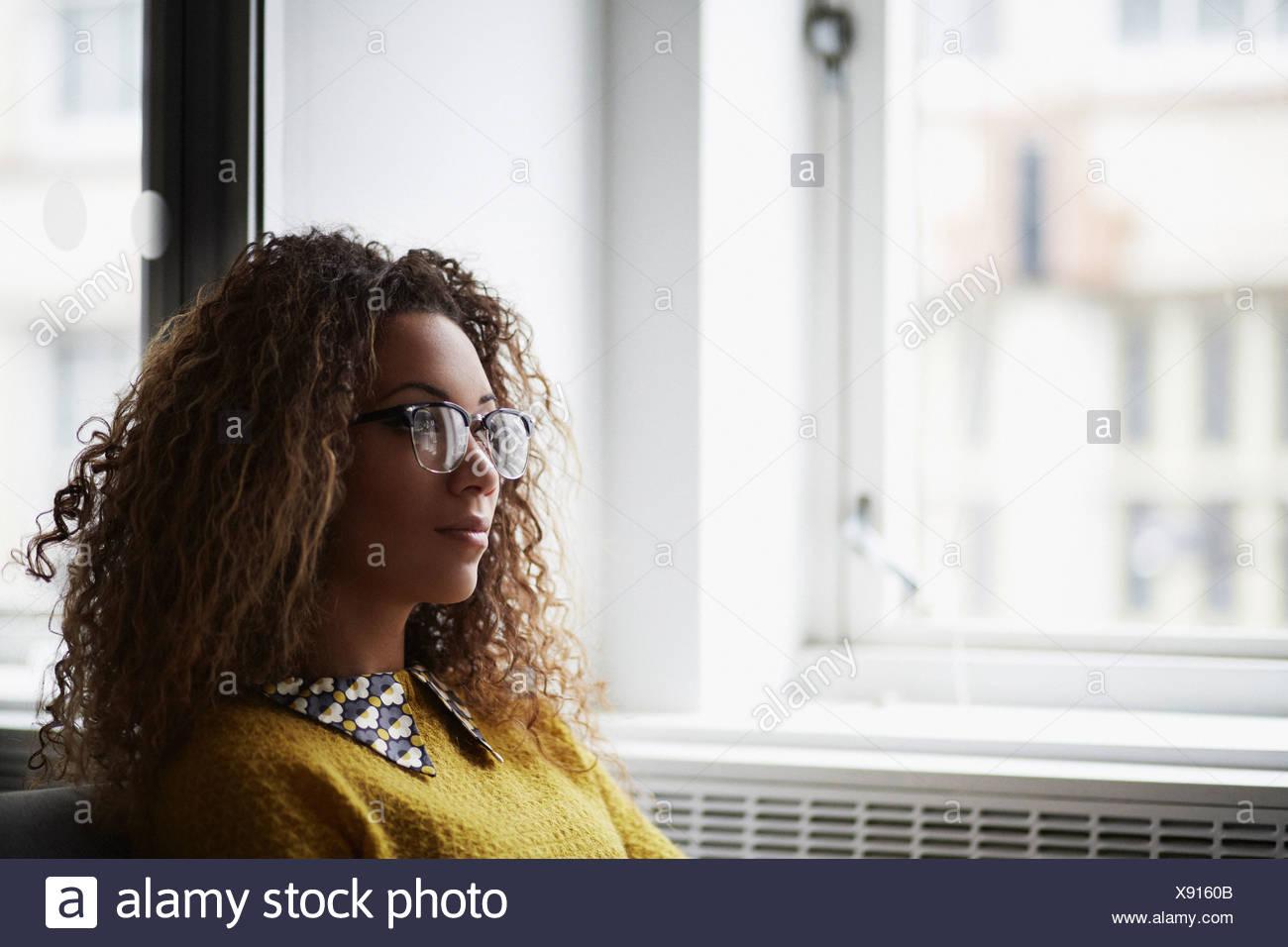 Portrait of female office worker wearing glasses - Stock Image
