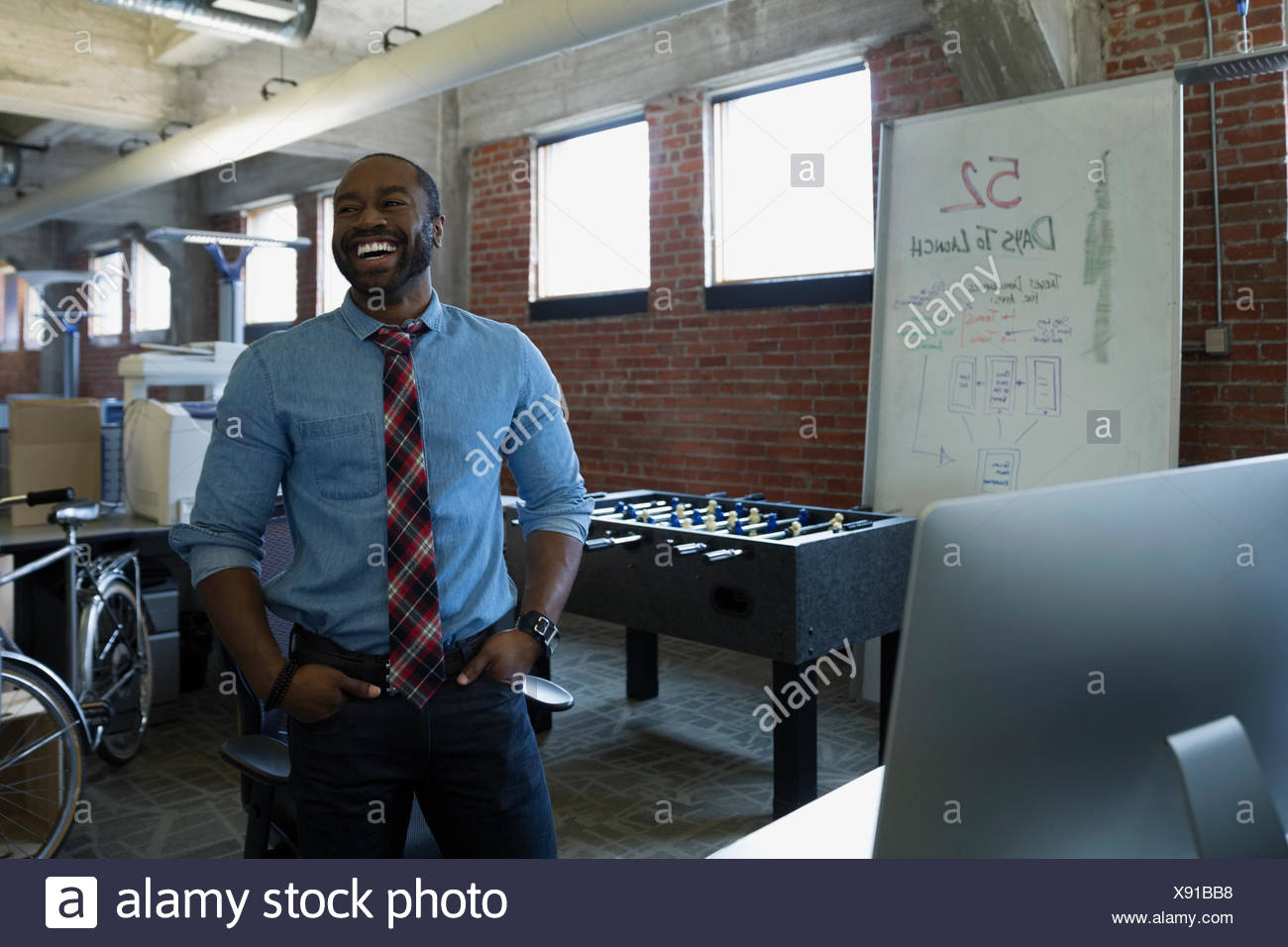 Laughing entrepreneur in new office - Stock Image