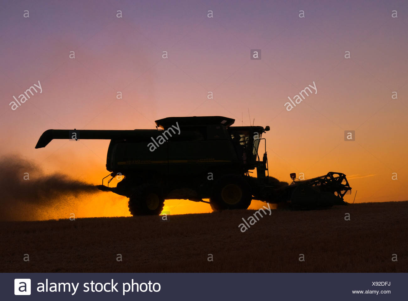Agriculture - A John Deere combine, silhouetted by the sunset, harvests barley / Palouse Region, near Pullman, Washington, USA. - Stock Image