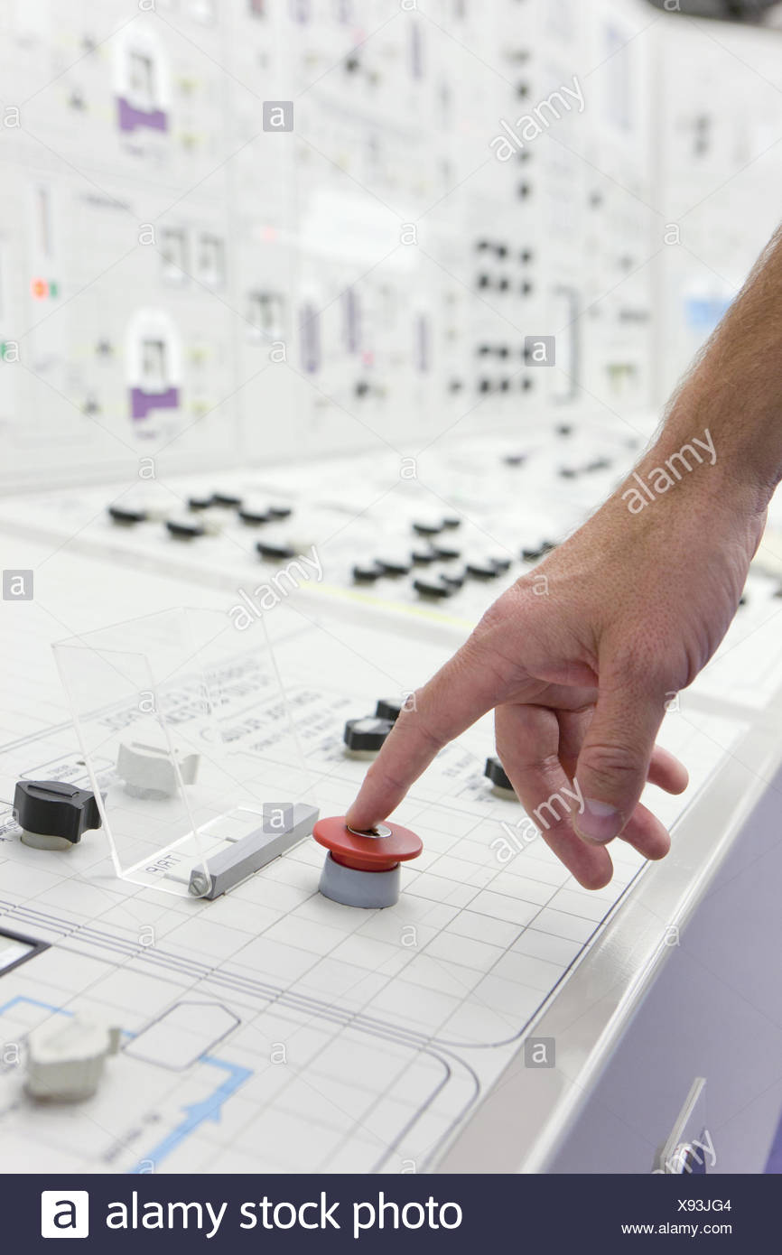 Man pushing red emergency button on control panel - Stock Image