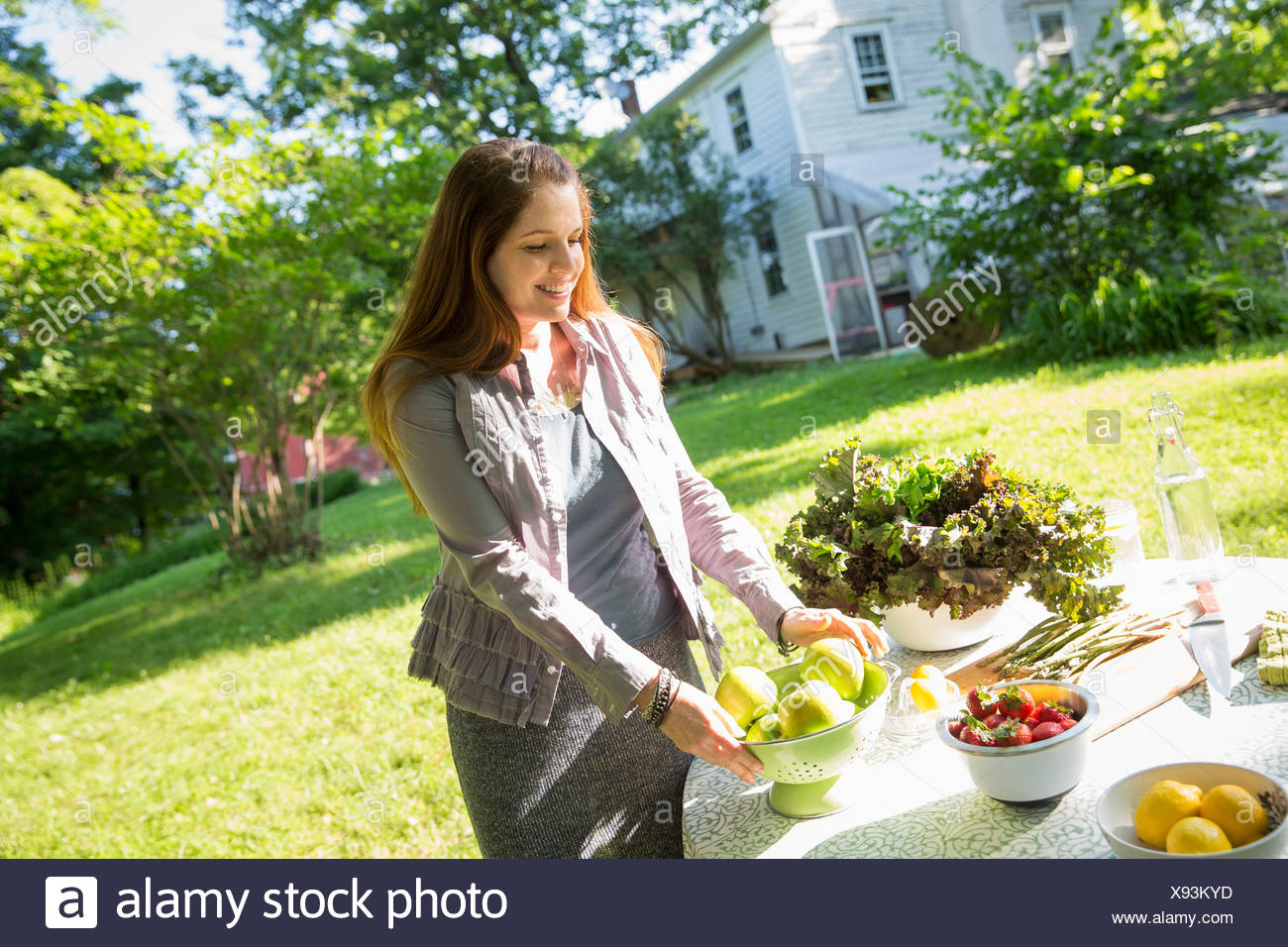 On farm woman in farmhouse garden preparing table fresh organic foods fresh vegetables salads bowls of fresh fruit for meal - Stock Image