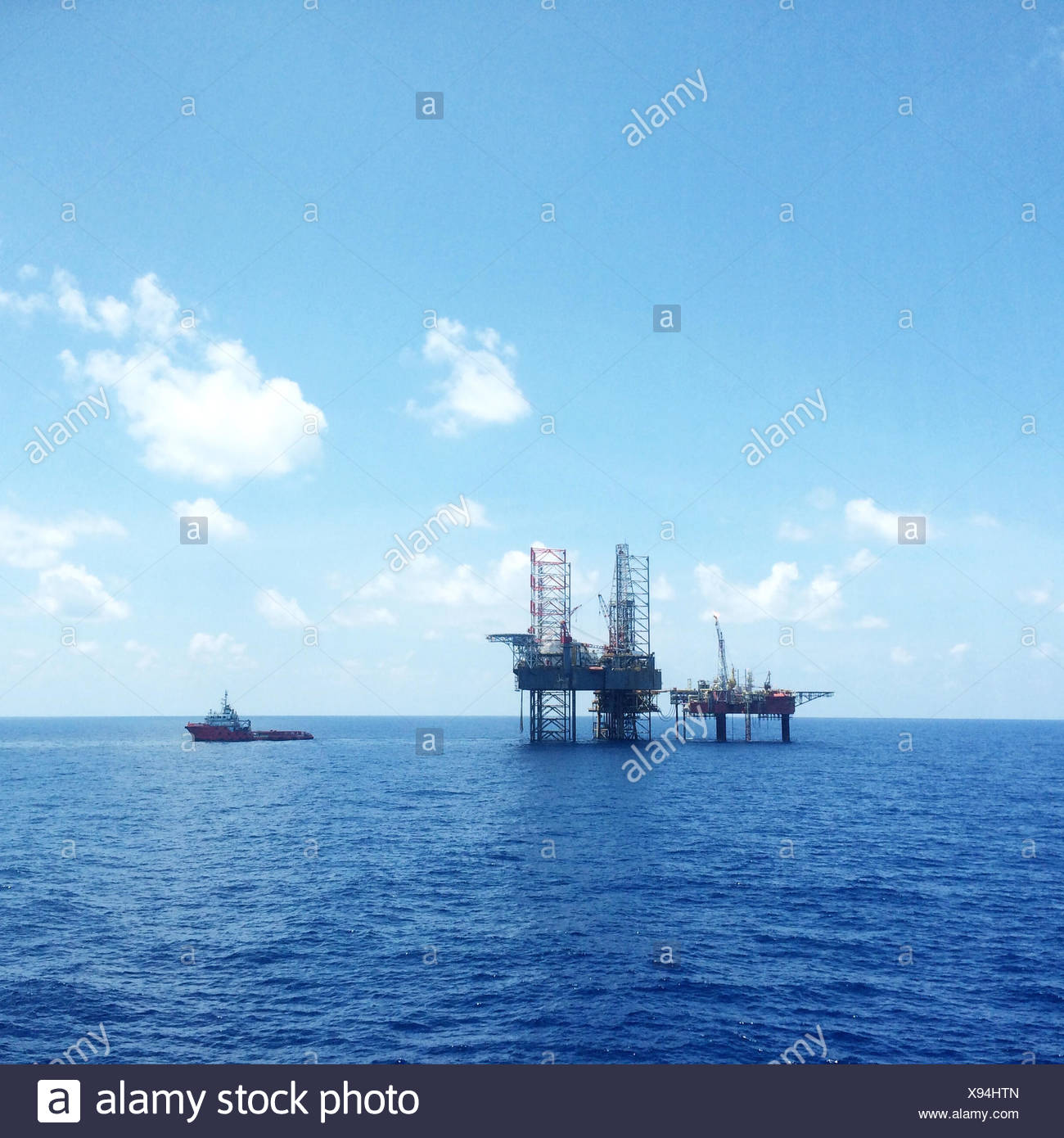 Oil and gas platform with offshore vessel transporting cargo - Stock Image
