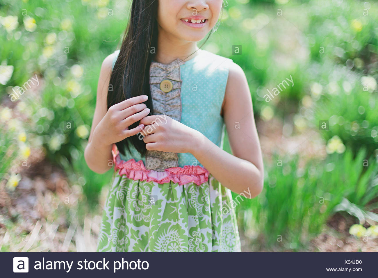 Girl (8-9) playing with hair - Stock Image