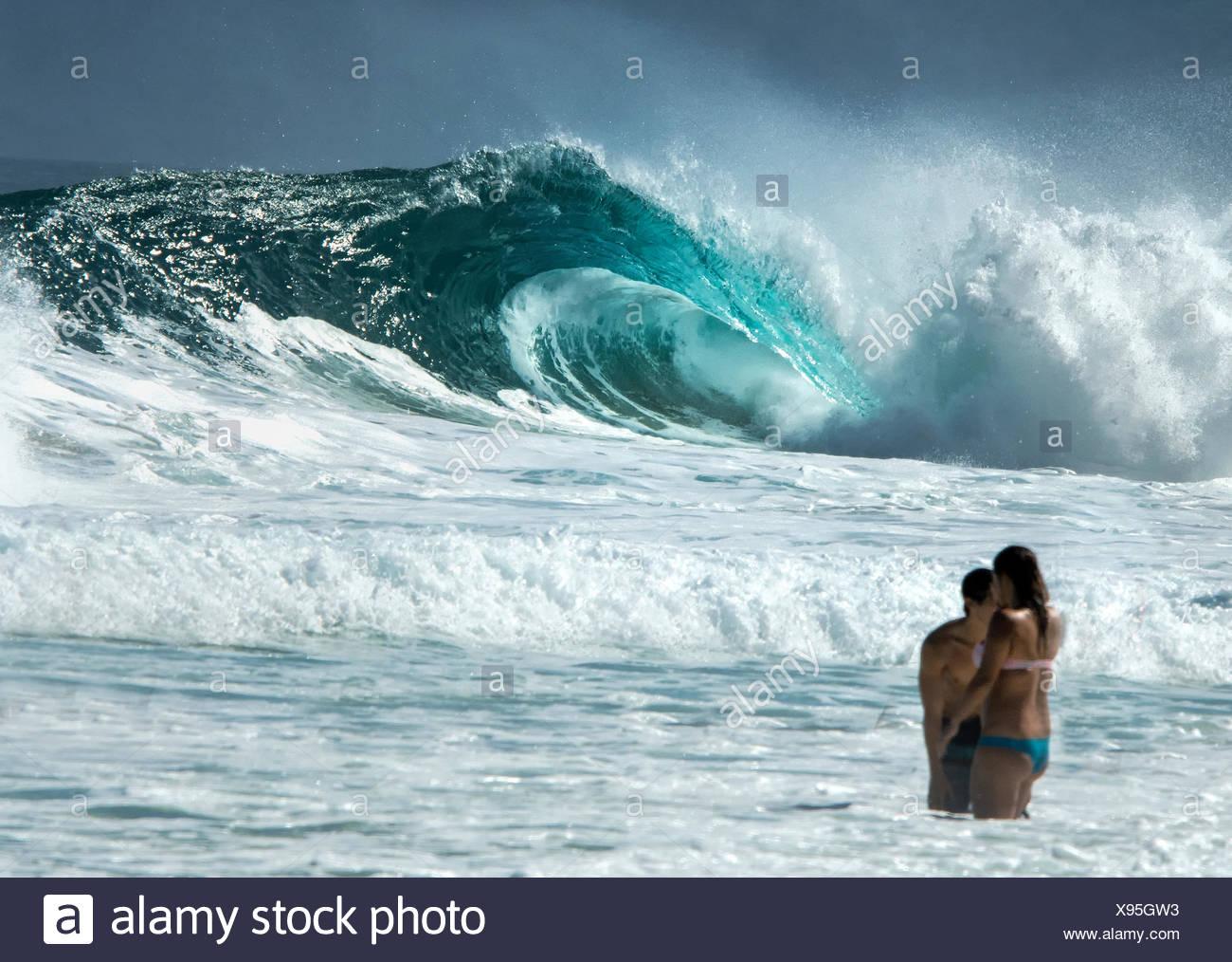 People standing in ocean and huge ocean wave in background - Stock Image