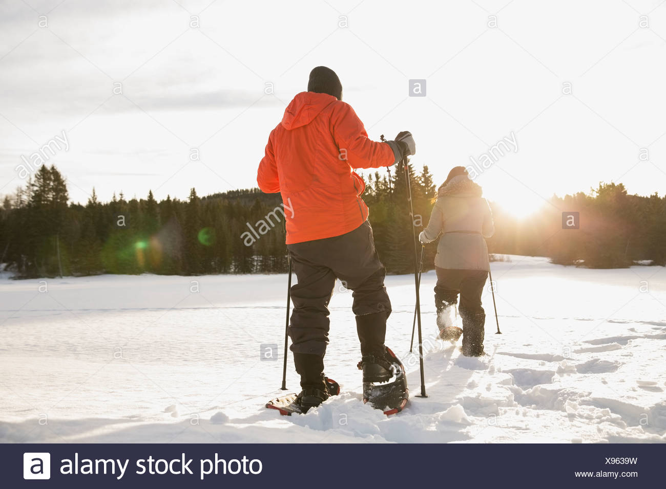 Rear view of couple snowshoeing - Stock Image