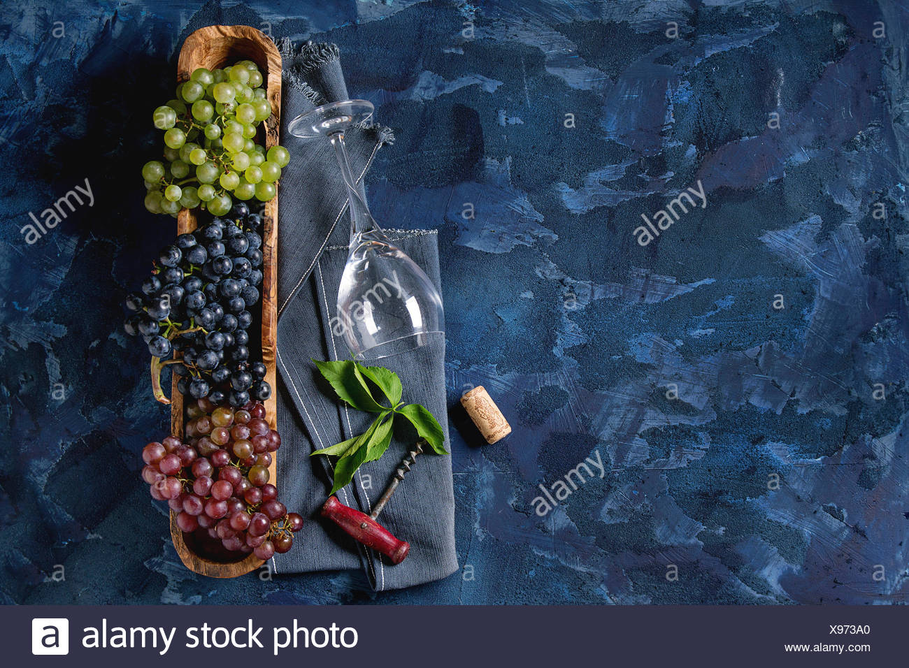 Variety of three type fresh ripe grapes dark blue, red and green in wooden bowl with empty laying wine glass, old corkscrew and green leaves over blue - Stock Image