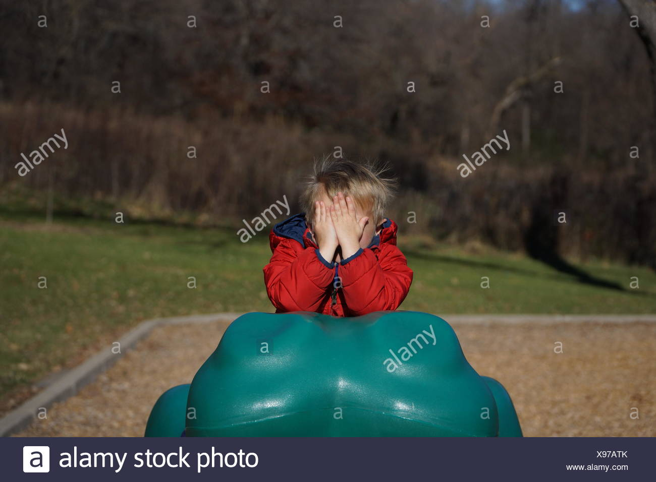 Boy Hiding Face At Playground - Stock Image