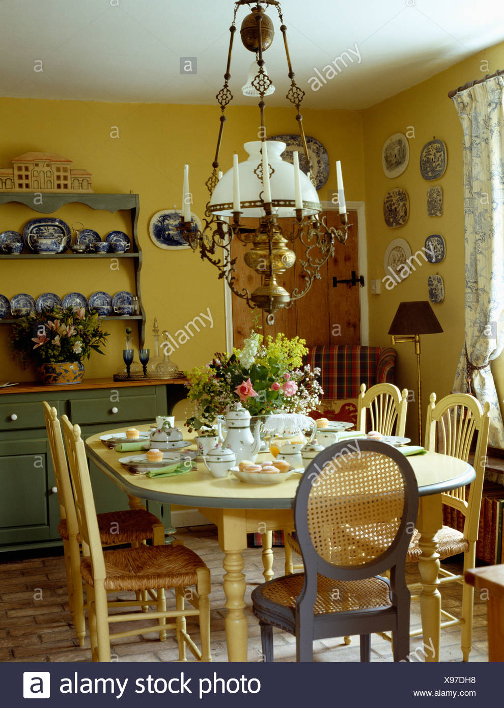 Glass Brass Victorian Lamp Above Cream Chairs And Table Set For Lunch In Pale Yellow
