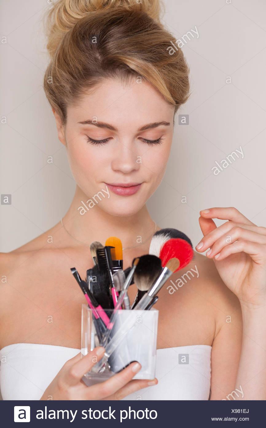 Beautiful woman holding assorted makeup brushes - Stock Image