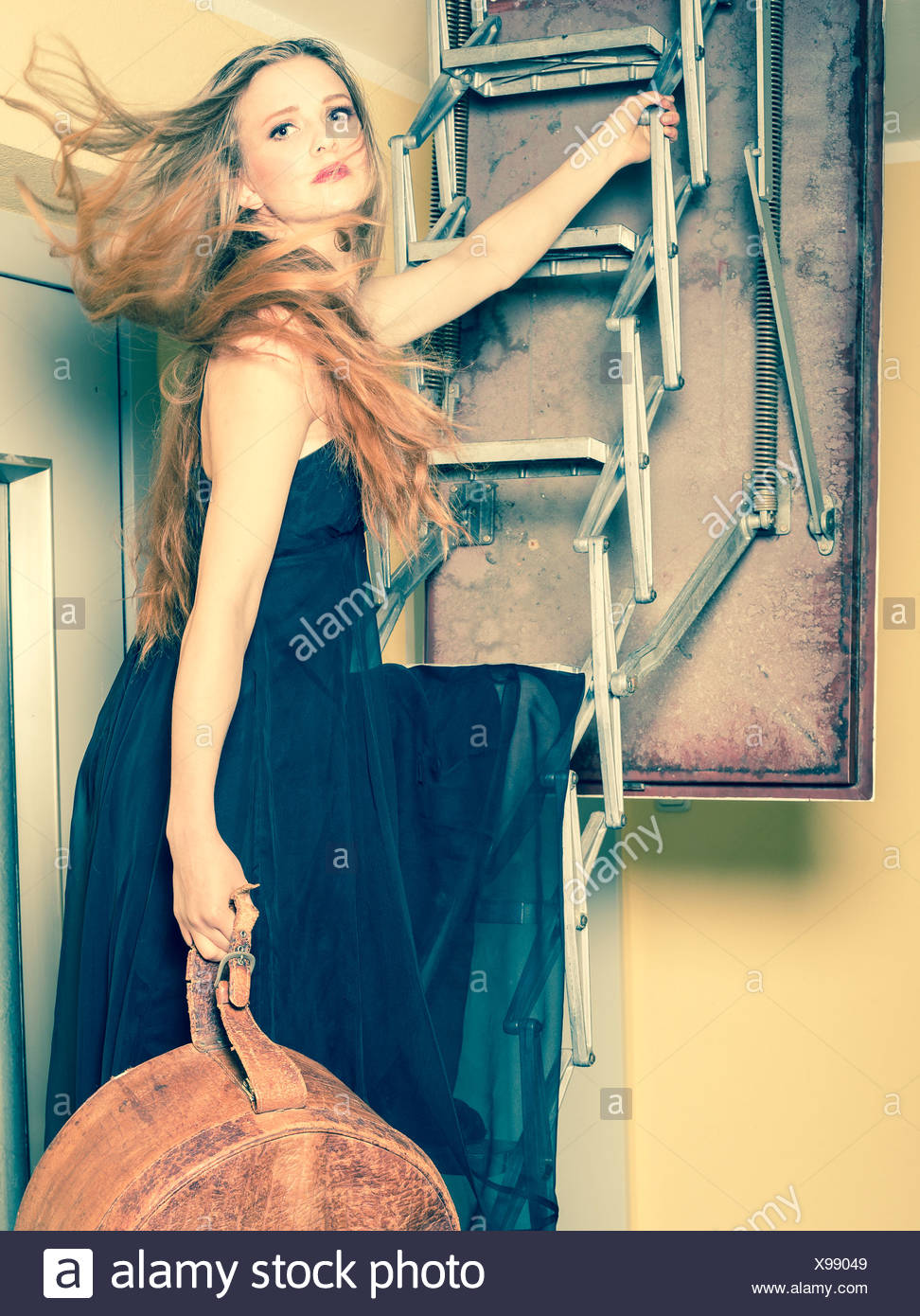 Portrait Of Young Woman With Old Hatbox Standing On Attic Ladder