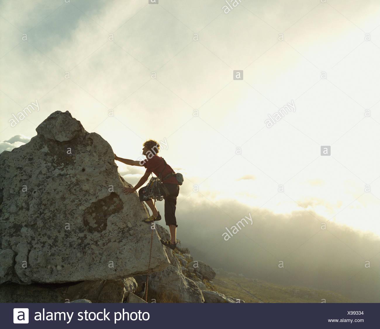 A mountain climber reaching the top of a mountain - Stock Image
