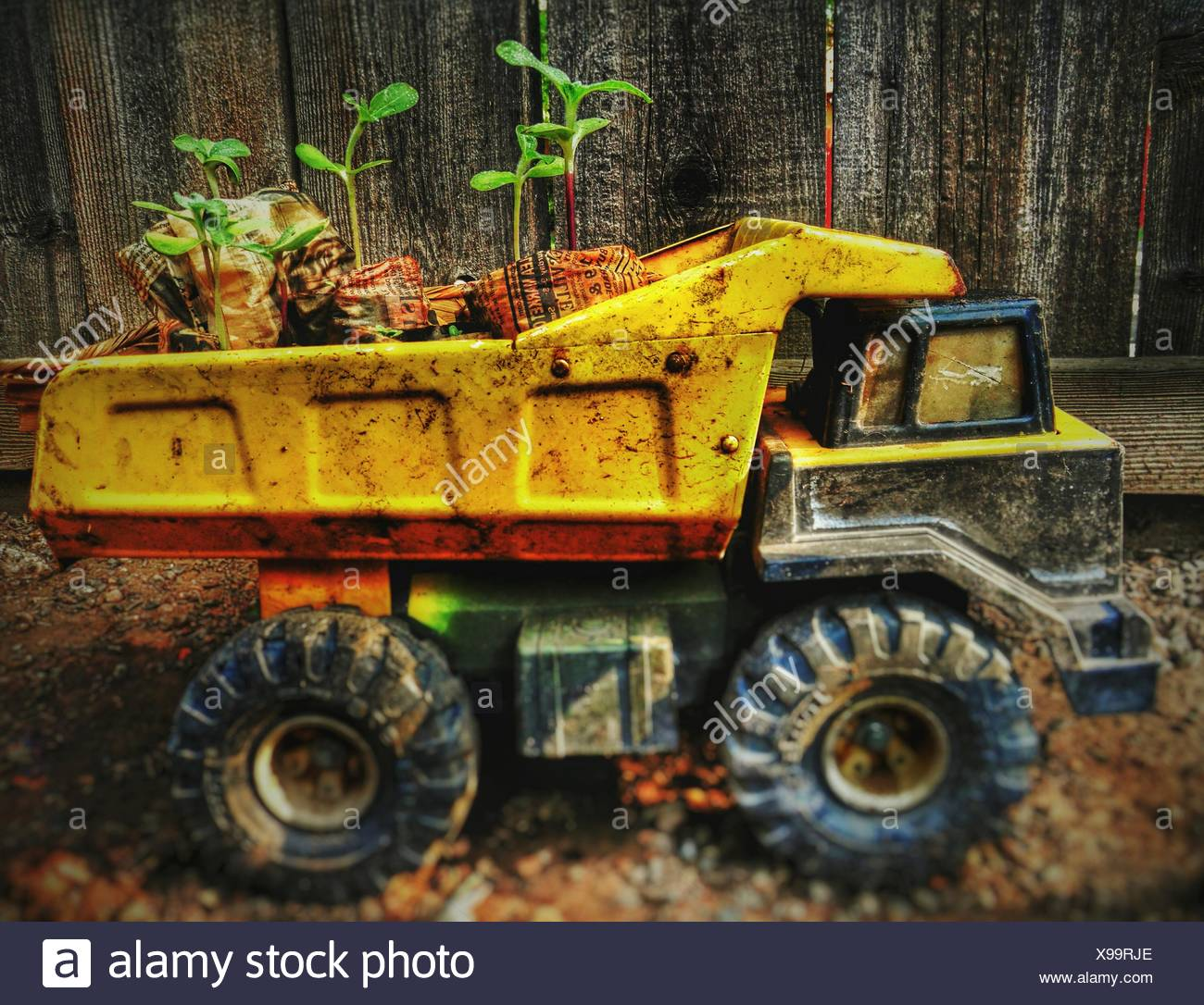 Close-Up Of Messy Toy Truck Against Wooden Fence - Stock Image