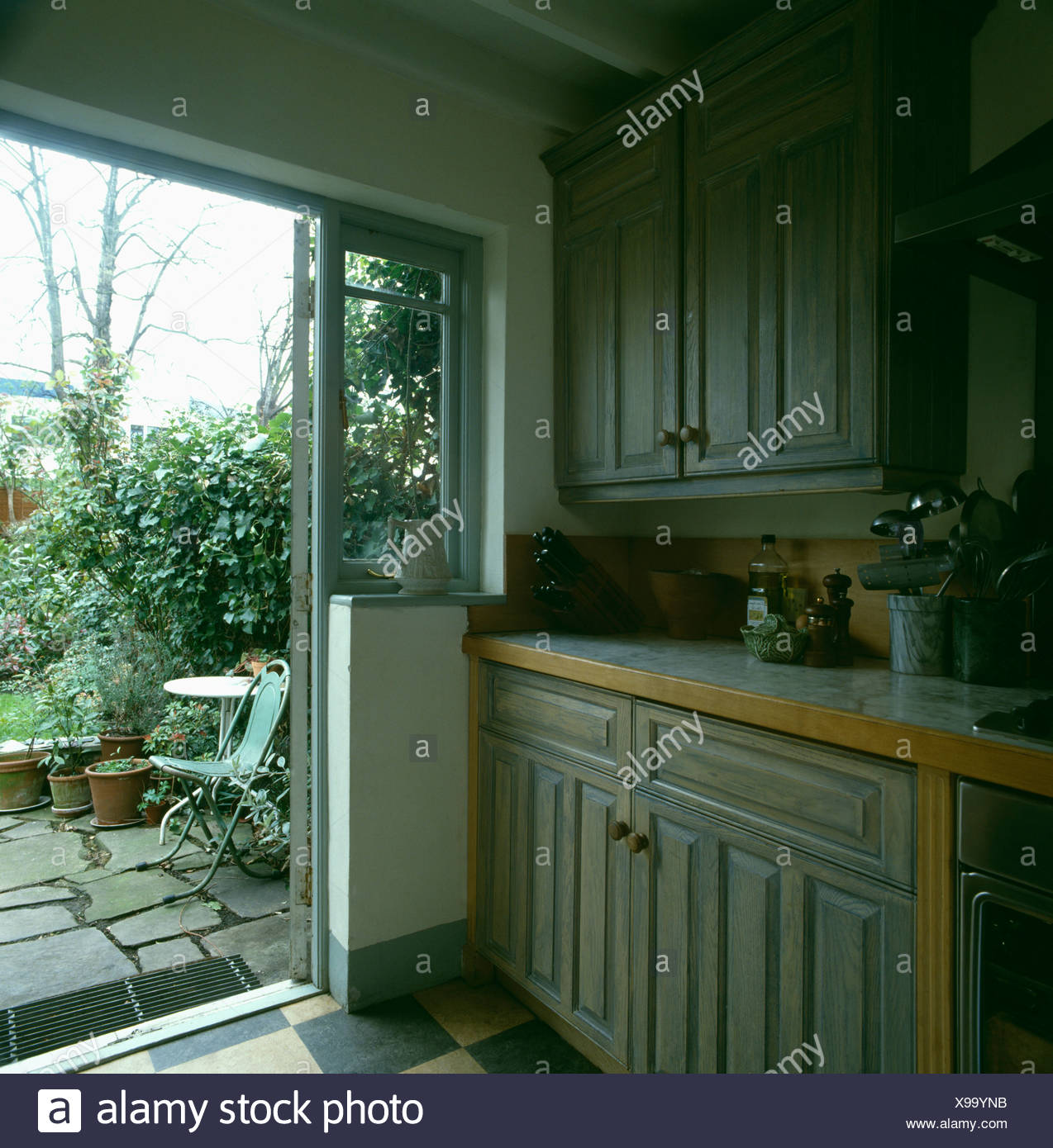 Pale Grey Wood Stain Units In Kitchen With Patio Door Open To The