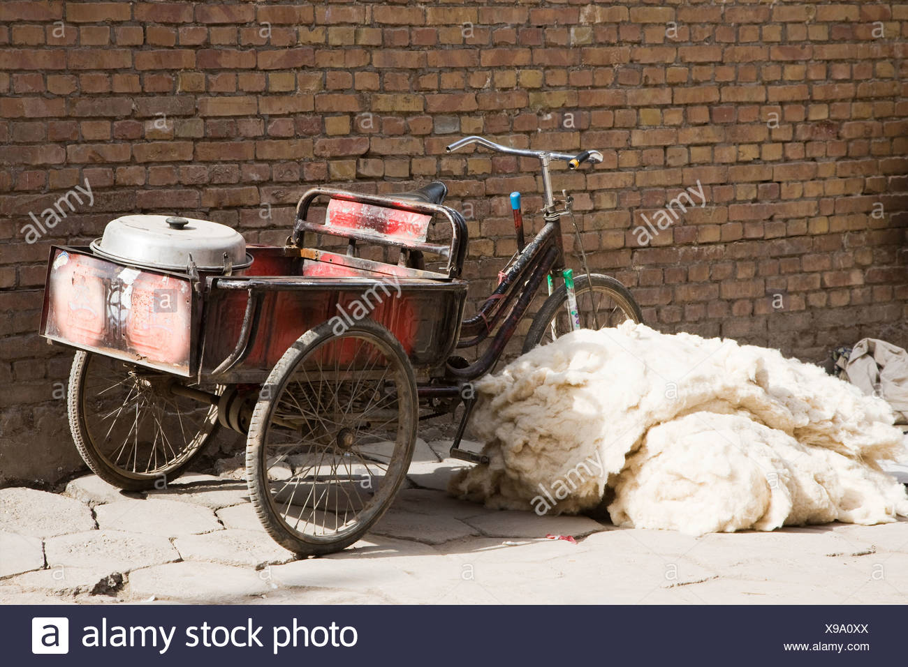 Bicycle next to pile of wool on footpath - Stock Image